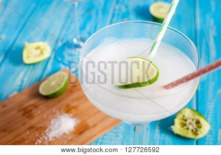 Classic frozen margarita cocktail in glass with salty rim on aqua wood table with limes and sea salt on wood plate near it.