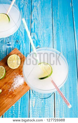 Classic Margarita Cocktail in margarita glass served with lime on aqua wood table. Cocktail ingredients: tequila, lime juice, orange liquor, ice and sea salt