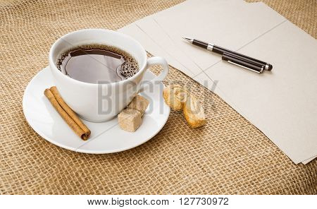 Cup of black coffee with foam cookie brown sugar craft paper pen and cinnamon stick on sackcloth background