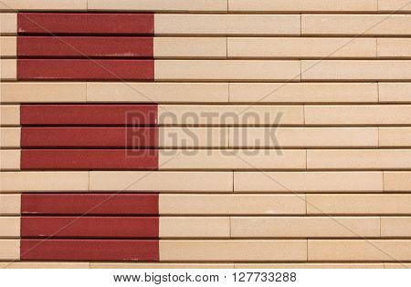 Beige and terracotta horizontal rectangles of reveted wall  form a geometric pattern