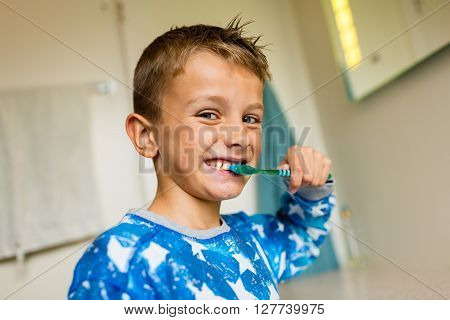 Close-up of young boy brushing his teeth with toothbrush while standing in bathroom with natural daylight.