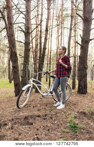 Beautiful young hipster girl in a red plaid shirt and leather backpack with a white cruiser retro bicycle in the forest among the pine trees