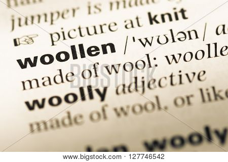 Close Up Of Old English Dictionary Page With Word Woollen.