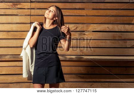 Beautiful And Young Woman Posing On Wooden Background