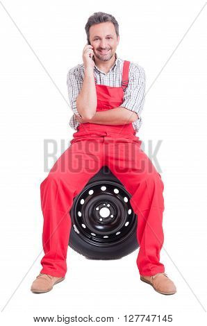 Mechanic Talking On The Phone Sitting On Wheel Tire