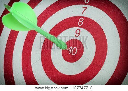Green dart arrow hitting in the target center of dartboard