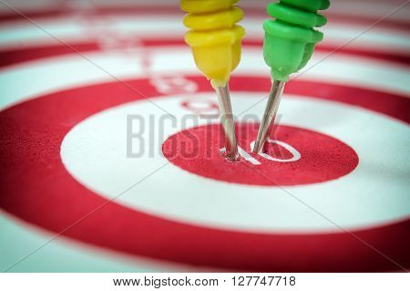 Dart arrows hitting in the target center of dartboard