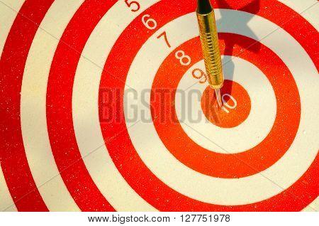 Dart arrow hitting in the target center of dartboard