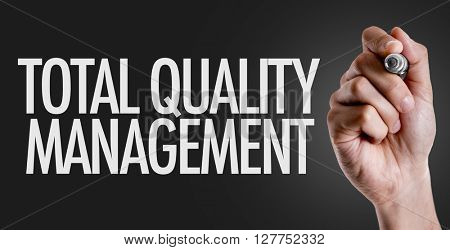 Hand writing the text: Total Quality Management