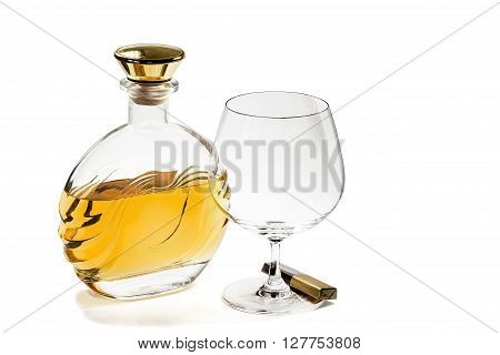Bottle of brandy and empty snifter with chocolate on white background