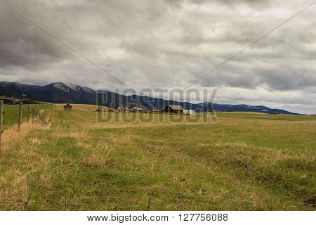 Landscape with cabin on a Montana Ranch. Mountains in background.