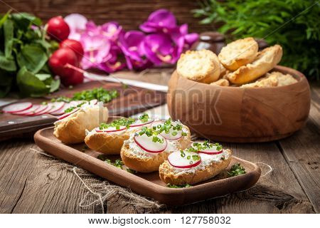 Toasts With Radish, Chives And Cottage Cheese On A Wooden Table.