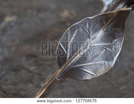 metal leaf on shabby wooden background, metal creation