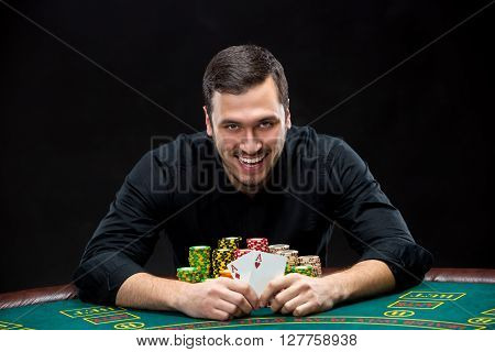 Happy poker player winning and holding a pair of aces sitting at a poker table with chips