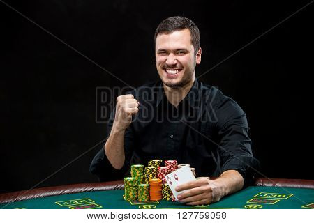 Happy poker player winning and holding a pair of aces, concept of winning or having the upper hand