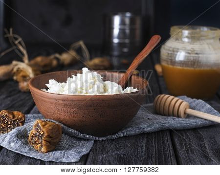 earthenware brown plate with white cottage cheese with dried fruits and nuts for healthy breakfast