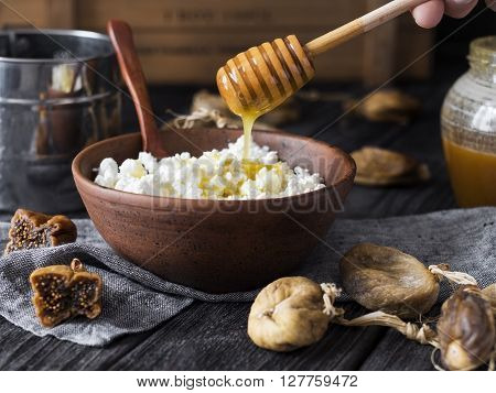 earthenware brown plate with white cottage cheese with dried fruits and nuts for healthy breakfast ** Note: Shallow depth of field