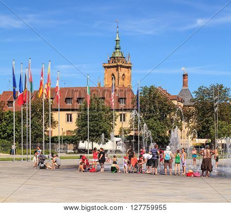 Colmar, France - 18 July, 2014: people at the fountain on Place Rapp square. Colmar is the third-largest commune of the Alsace region in north-eastern France renowned for its well preserved old town.