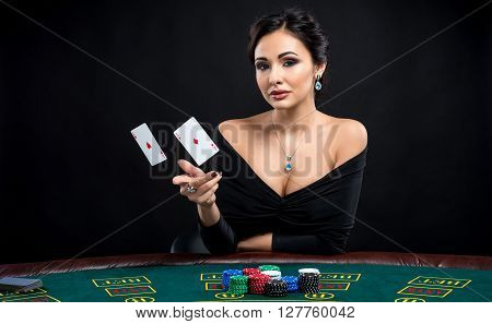 sexy woman with poker cards. Female player in a beautiful black dress and throwing two aces