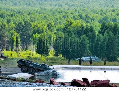 Nizhniy Tagil, Russia - July 12. 2008: BTR-82A armoured personnel carrier moves in water and shoots on shooting demonstration range