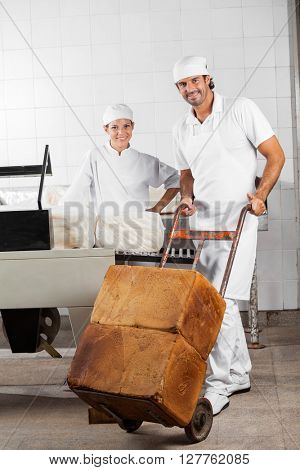 Worker Pushing Bread Loaves On Pushcart While Coworker Smiling