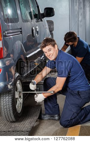Happy Technician Fixing Car Tire At Workshop