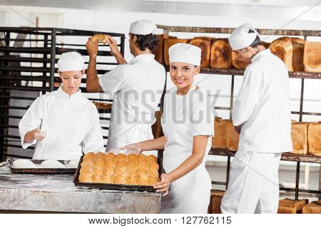 Confident Baker Showing Breads In Bakery