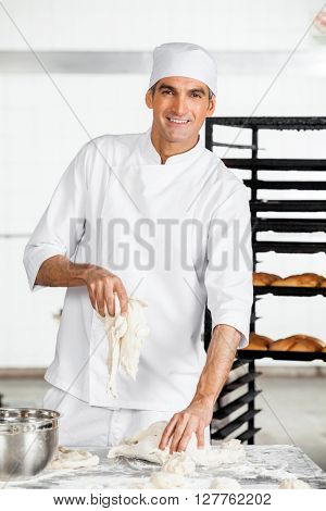 Confident Male Baker Kneading Dough At Table