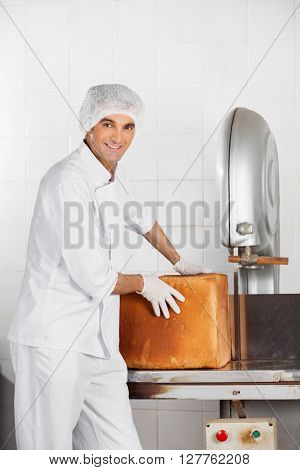 Baker With Bread Loaf Standing At Cutting Machine