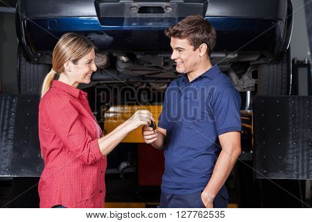 Happy Customer Giving Car Key To Mechanic