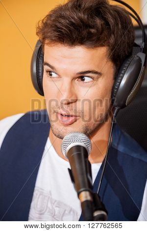 Man Singing While Wearing Headphones In Recording Studio