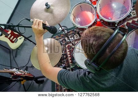 Male Drummer Adjusting Microphone In Recording Studio