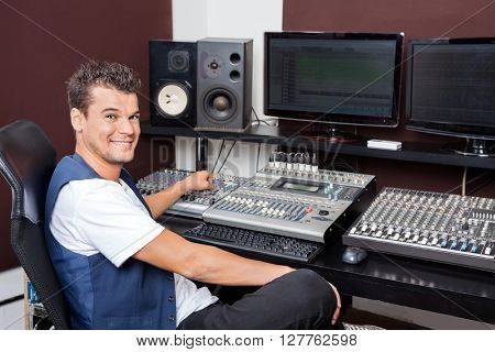 Portrait Of Young Man Mixing Audio In Recording Studio