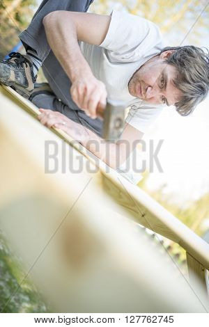 Low angle view of young man using a hammer or mallet to nail a nail into a wooden structure he is building in a DIY conceptual image.