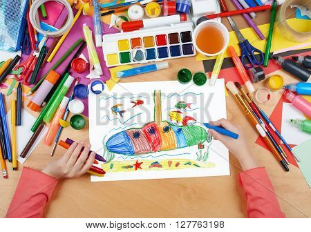 submarine and sea life child drawing , top view hands with pencil painting picture on paper, artwork workplace