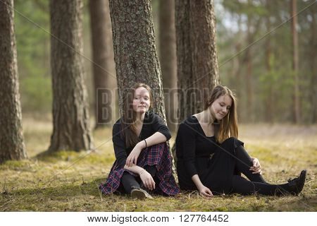 Teenage girls best friends sitting in the forest.