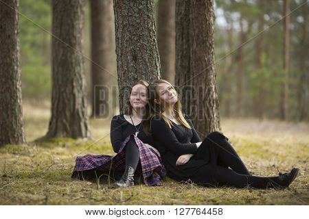 Cute girls friends sitting in the forest.