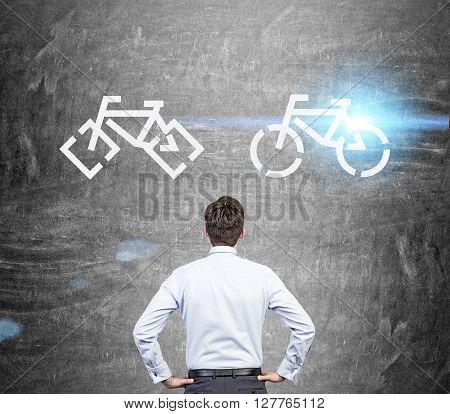 Rearview of businessman looking at bicycle sketches on chalkboard deciding which one to choose. Commuting concept