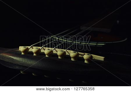 six-string acoustic guitar on a dark background