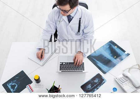 Doctor Using Laptop And Reflecting