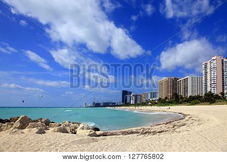 Miami Beach USA - May 14 2013: Scene of the crowded beach. People having fun sunbathing and swimming in the shallow water. Skyline in the back.