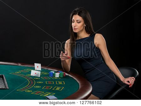 sexy woman with poker cards and chips. Female player in a beautiful black dress, throws a card. Two aces