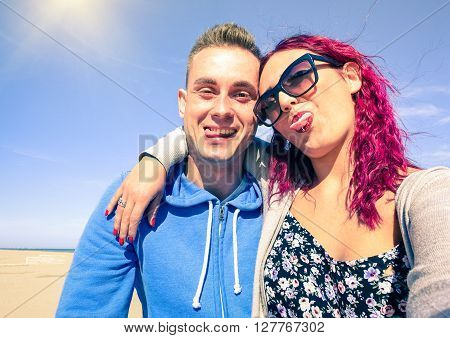 Young couple grimacing is taking selfie on the beach - Best friends with funny face self photo at summer vacation on blue sky background - Modern concept of fun using new phone technology and trends