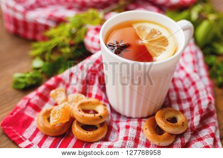 Cup of hot tea with lemon and anise star. White mug with hot beverage on plaid red towel with ginger pieces and cookies.