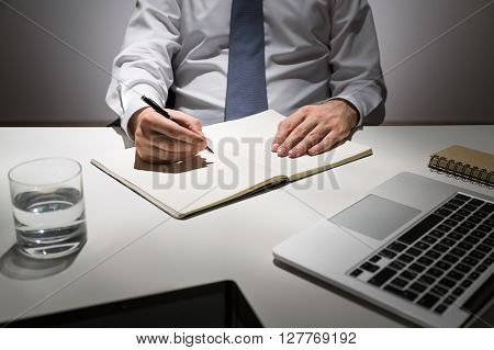 Businessman Writing In Journal