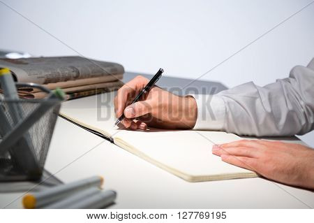 Sideview of businessperson hands writing in journal on office desk