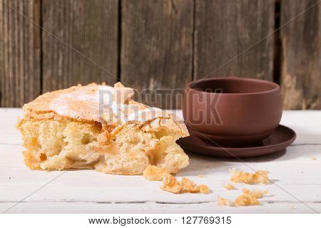 Piece of pie and clay cup against boards. Close up