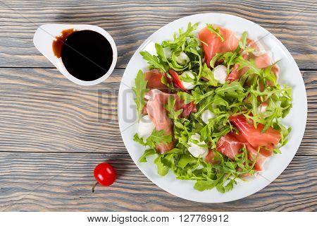 Arugula prosciutto mozzarella salad on a white dish sandwich with ham and balsamic vinegar in a gravy boat on a wooden table top view studio lights