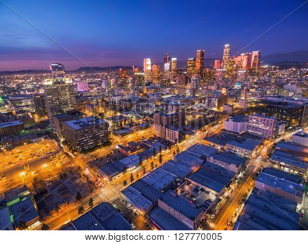 Illuminated streets leading to downtown Los Angeles skyline at twilight dusk night. Aerial perspective.