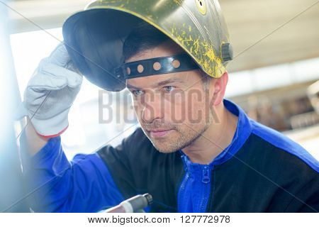 Man lifting welding mask